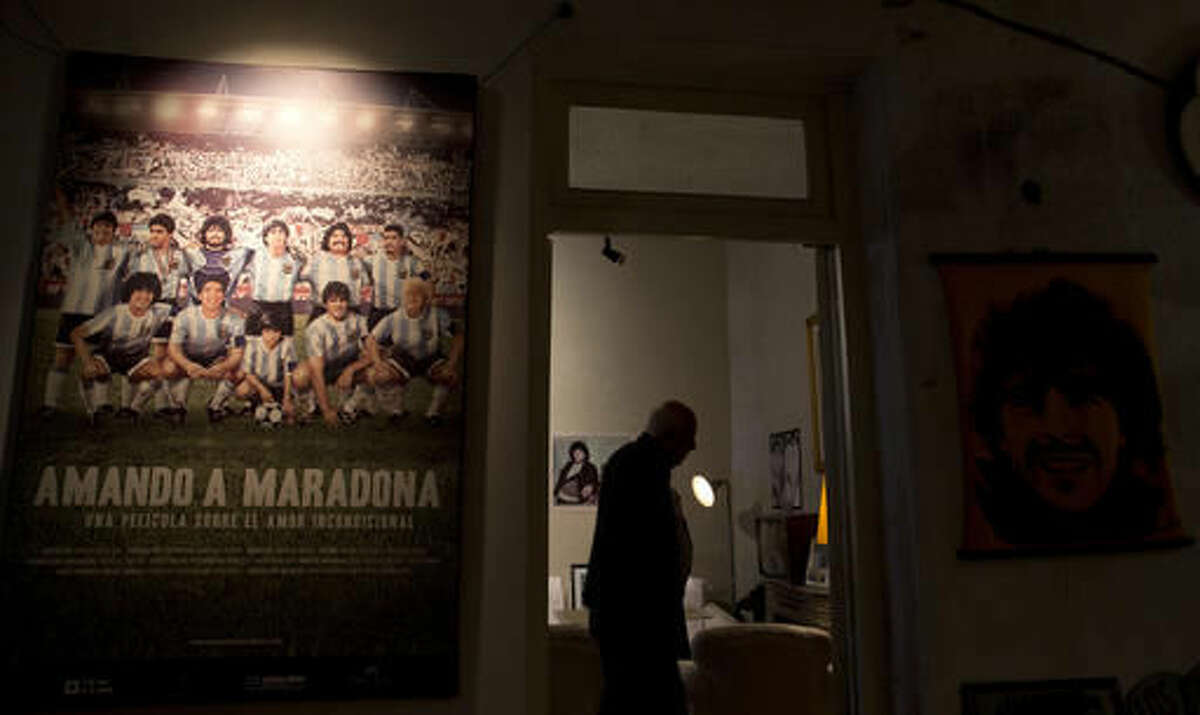Visitor Alberto Perez stands inside the living room of the old home of soccer star Diego Armando Maradona in Buenos Aires, Argentina, Thursday, Oct. 27, 2016. The home where Maradona lived as a teenager while playing for Argentinos Juniors recently opened to the public, becoming a new shrine for the soccer legend. (AP Photo/Natacha Pisarenko)