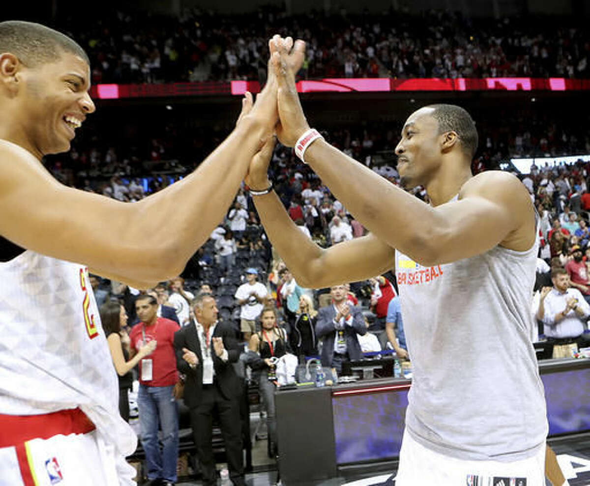 Atlanta Hawks' Dwight Howard celebrates a 114-99 victory over the Washington Wizards with Edy Tavares in the home opener of an NBA basketball game Thursday, Oct. 27, 2016, in Atlanta. (Curtis Compton/Atlanta Journal-Constitution via AP)