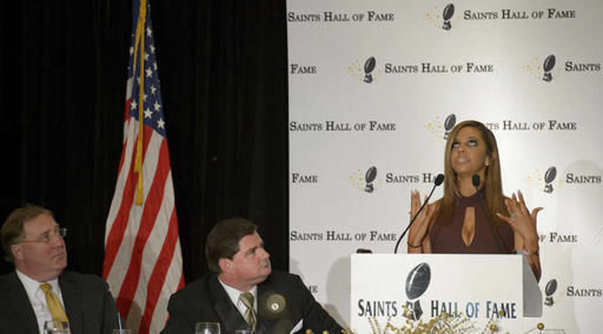 Looking up to the heavens, Racquel Smith speaks to her husband, slain New Orleans Saints defensive end Will Smith, and tells him that she is proud of him, at the New Orleans Saints Hall of Fame luncheon in Kenner, La., Friday, Oct. 28, 2016. Dennis Lauscha, left, president of the Saints, and Ken Trahan, a sportswriter and master of ceremonies, listen. (Matthew Hinton/The Advocate via AP)