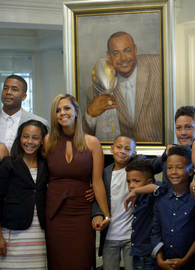 Family members and children of slain New Orleans Saints defensive end Will Smith, including his wife, Racquel Smith, third from left, pose by a portrait of Smith that was unveiled at the NFL football team's Hall of Fame luncheon, where he was enshrined into the team's hall of fame, in Kenner, La., Friday, Oct. 28, 2016. (Matthew Hinton/The Advocate via AP)