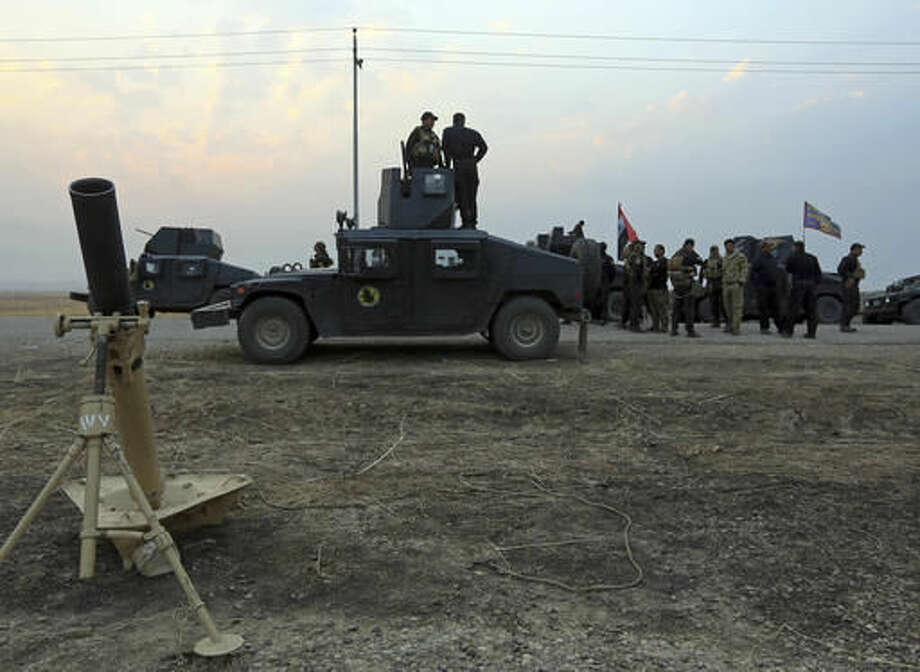 Iraq's elite counterterrorism forces prepare to attack Islamic State positions as fighting to retake the extremist-held city of Mosul enters its second week, in the village of Tob Zawa, outside Mosul, Monday, Oct. 24, 2016. A convoy of special forces advanced toward the village of Tob Zawa, Monday, encountering roadside bombs and trading heavy fire with the militants. Loudspeakers on the Humvees blared Iraqi patriotic music as they pushed toward the village. (AP Photo/Khalid Mohammed)