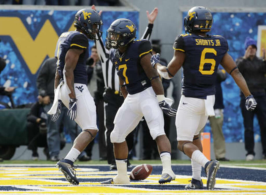 West Virginia running back Rushel Shell (7) celebrates with wide receiver Shelton Gibson (1) after he scores a touchdown during the first half of an NCAA college football game against TCU, Saturday, Oct. 22, 2016, in Morgantown, W.Va. (AP Photo/Raymond Thompson)