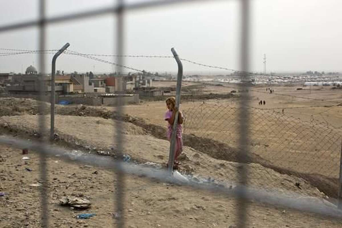 A girl stands inside a camp for displaced families in Dibaga, near Mosul, Iraq, Monday, Oct. 24, 2016. The campaign to retake Mosul comes after months of planning and involves more than 25,000 Iraqi troops, Kurdish forces, Sunni tribal fighters and state-sanctioned Shiite militias. It is expected to take weeks, if not months, to drive Islamic State militants out of Iraq's second largest city, which is still home to more than a million people.(AP Photo/Marko Drobnjakovic)