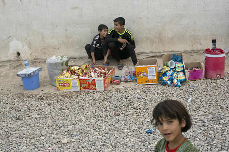 Two youths sell snacks at a camp for displaced families in Dibaga, near Mosul, Iraq, Monday, Oct. 24, 2016. The campaign to retake Mosul comes after months of planning and involves more than 25,000 Iraqi troops, Kurdish forces, Sunni tribal fighters and state-sanctioned Shiite militias. It is expected to take weeks, if not months, to drive IS out of Iraq's second largest city, which is still home to more than a million people.(AP Photo/Marko Drobnjakovic)