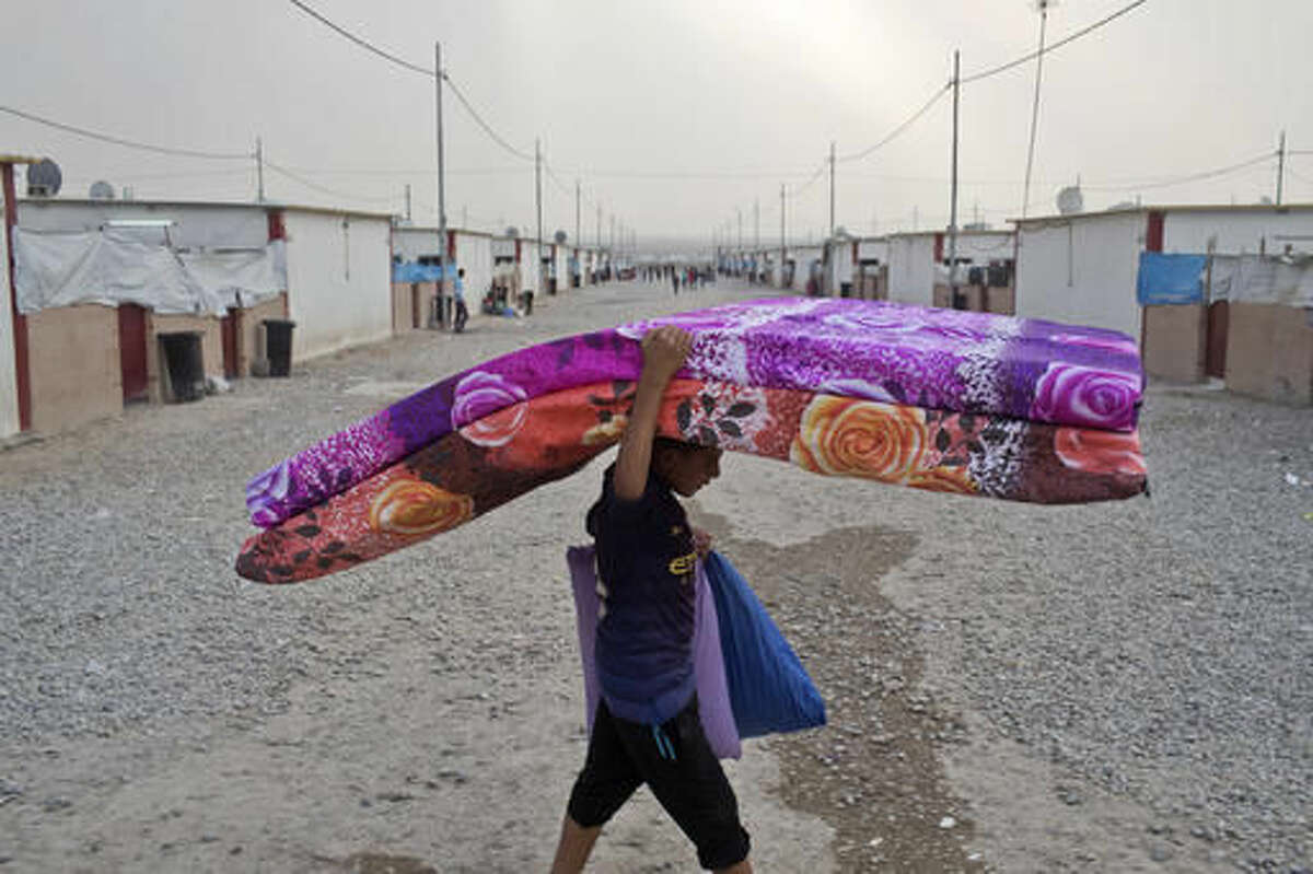A boy carries mattresses at a camp for displaced families in Dibaga, near Mosul, Iraq, Monday, Oct. 24, 2016. The campaign to retake Mosul comes after months of planning and involves more than 25,000 Iraqi troops, Kurdish forces, Sunni tribal fighters and state-sanctioned Shiite militias. It is expected to take weeks, if not months, to drive Islamic State militants out of Iraq's second largest city, which is still home to more than a million people.(AP Photo/Marko Drobnjakovic)