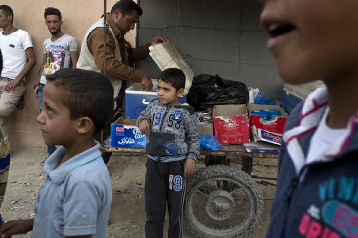A boy waits for customers as he sells snacks at a camp for displaced families in Dibaga, near Mosul, Iraq, Monday, Oct. 24, 2016. The campaign to retake Mosul comes after months of planning and involves more than 25,000 Iraqi troops, Kurdish forces, Sunni tribal fighters and state-sanctioned Shiite militias. It is expected to take weeks, if not months, to drive Islamic State militants out of Iraq's second largest city, which is still home to more than a million people.(AP Photo/Marko Drobnjakovic)
