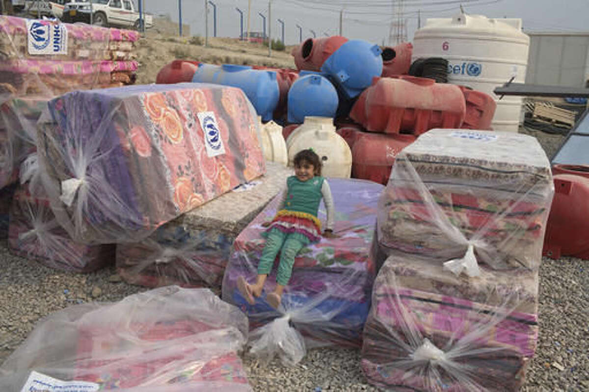 A girl sits on a pile of mattresses at a camp for displaced families in Dibaga, near Mosul, Iraq, Monday, Oct. 24, 2016. The campaign to retake Mosul comes after months of planning and involves more than 25,000 Iraqi troops, Kurdish forces, Sunni tribal fighters and state-sanctioned Shiite militias. It is expected to take weeks, if not months, to drive Islamic State militants out of Iraq's second largest city, which is still home to more than a million people.(AP Photo/Marko Drobnjakovic)