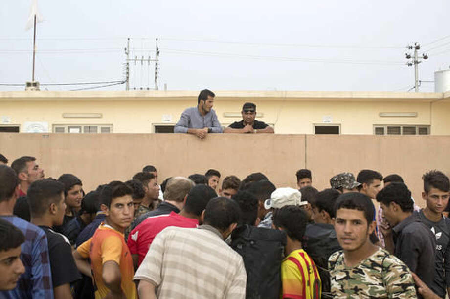 People gather as aid is being distributed at a camp for displaced families in Dibaga, near Mosul, Iraq, Monday, Oct. 24, 2016. The campaign to retake Mosul comes after months of planning and involves more than 25,000 Iraqi troops, Kurdish forces, Sunni tribal fighters and state-sanctioned Shiite militias. It is expected to take weeks, if not months, to drive Islamic State militants out of Iraq's second largest city, which is still home to more than a million people.(AP Photo/Marko Drobnjakovic)