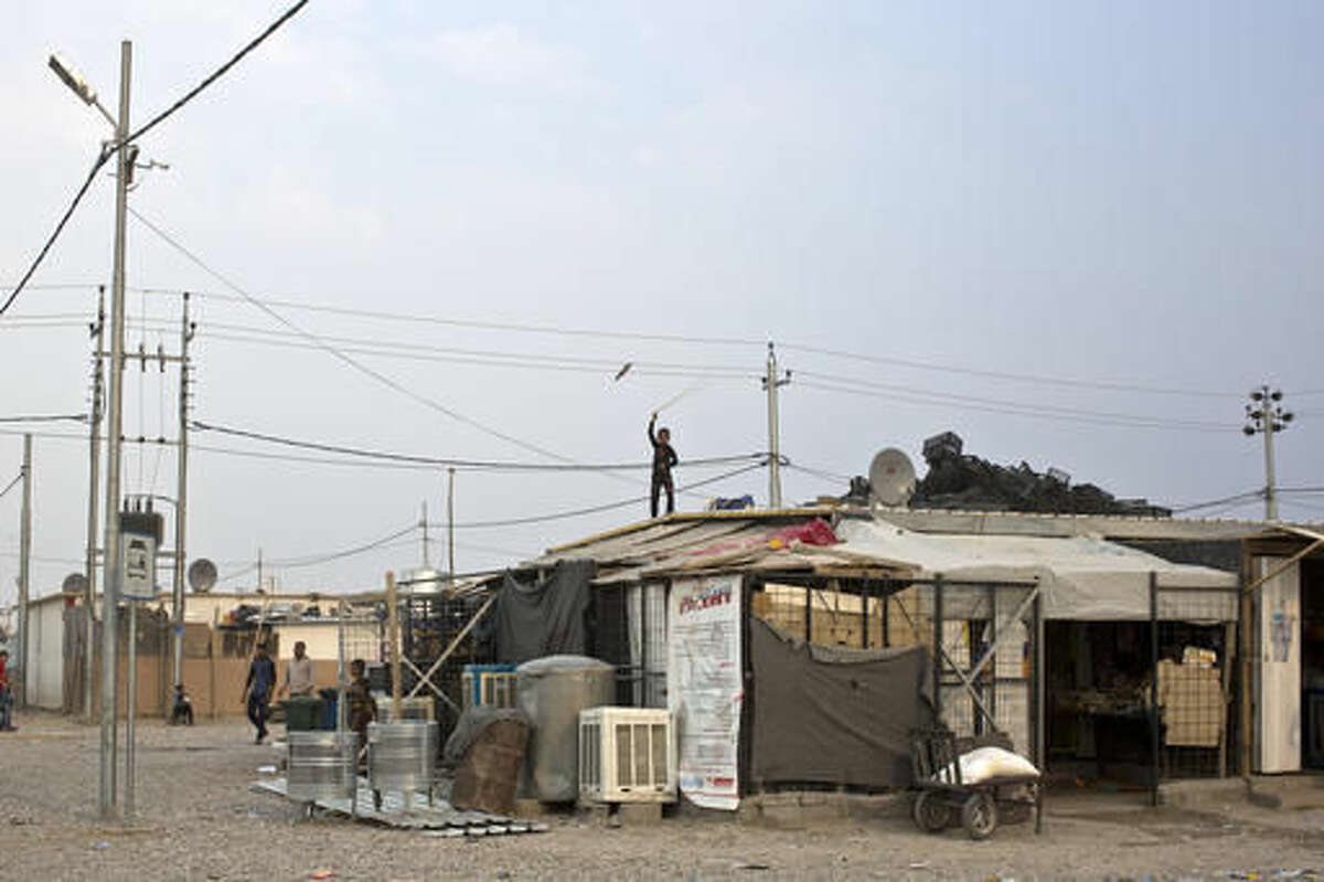 A boy plays with a rope as he stands atop a makeshift convenience store at a camp for displaced families in Dibaga, near Mosul, Iraq, Monday, Oct. 24, 2016. The campaign to retake Mosul comes after months of planning and involves more than 25,000 Iraqi troops, Kurdish forces, Sunni tribal fighters and state-sanctioned Shiite militias. It is expected to take weeks, if not months, to drive Islamic State militants out of Iraq's second largest city, which is still home to more than a million people.(AP Photo/Marko Drobnjakovic)