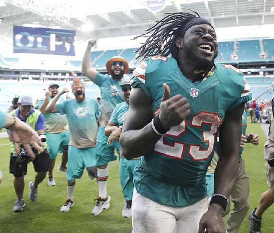 Miami Dolphins running back Jay Ajayi (23) is congratulated as he leaves the field, at the end of an NFL football game against the Buffalo Bills, Sunday, Oct. 23, 2016, in Miami Gardens, Fla. Ajayi tied an NFL record by surpassing 200 yards rushing for the second game in a row, helping the Miami Dolphins rally past the Buffalo Bills 28-25. (AP Photo/Lynne Sladky)