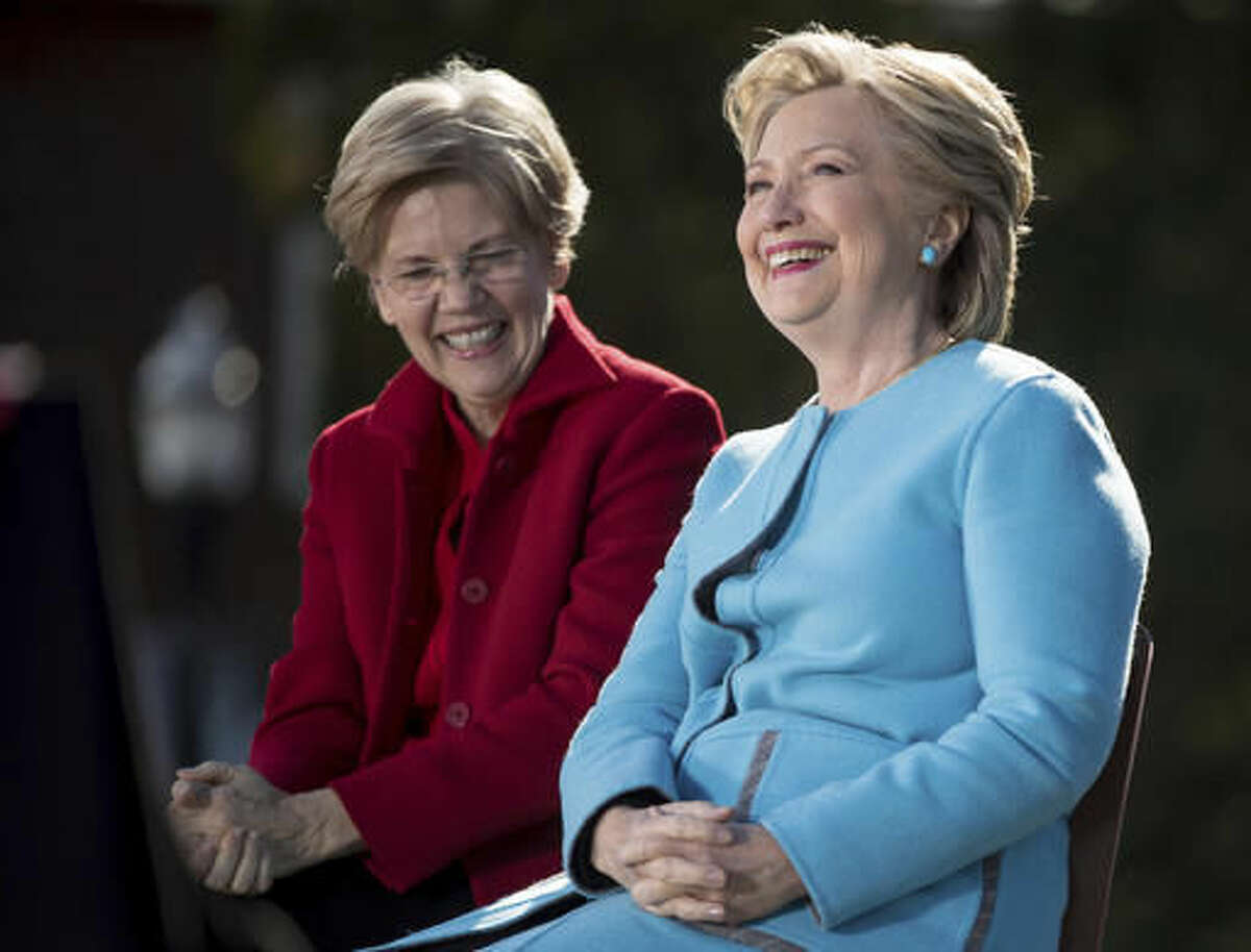 Democratic presidential candidate Hillary Clinton, accompanied by Sen. Elizabeth Warren, D-Mass., smiles as they sit on stage at a rally at St. Anselm College in Manchester, N.H., Monday, Oct. 24, 2016. (AP Photo/Andrew Harnik)