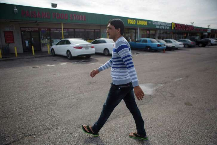 Shaor Ahmad Safi walks through his new neighborhood in Gulfton, Thursday, Dec. 1, 2016, in Houston. Shaor worked as a translator for the U.S. military in Kandahar Province. Shaor just arrived in the United States two weeks ago.