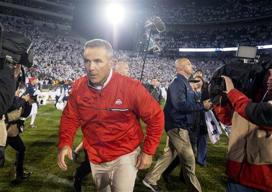Ohio State coach Urban Meyer runs off the field after shaking hands with Penn State coach James Franklin, background, after an NCAA college football game Saturday, Oct. 22, 2016, in State College, Pa. Penn State won 24-21. (Abby Drey/Centre Daily Times via AP)