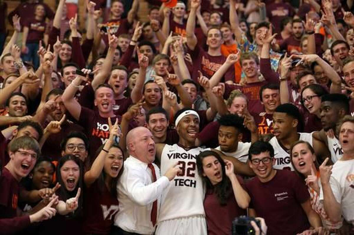 FILE - In this March 16, 2016, file photo, Virginia Tech head coach Buzz Williams and Zach LeDay (32) center, celebrate with fellow players and fans after the Virginia Tech - Princeton NIT opening round NCAA college basketball game in Blacksburg Va. Buzz Williams has coached Virginia Tech for two seasons with low expectations as an ally. He won't have that card to play this year because of what last season produced. (Matt Gentry/The Roanoke Times via AP, File)