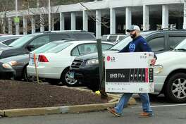Shopper Matt Montalvo, of Fairfield, carries a HD TV to his car after shopping for Black Friday deals at the Westfield Trumbull Mall on Nov. 25.