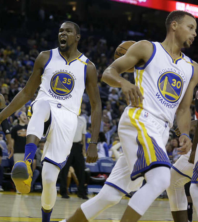 Golden State Warriors' Kevin Durant, left, celebrates after scoring against the Portland Trail Blazers during the second half of a preseason NBA basketball game against the Portland Trail Blazers Friday, Oct. 21, 2016, in Oakland, Calif. At right is Warriors' Stephen Curry (30). (AP Photo/Ben Margot)