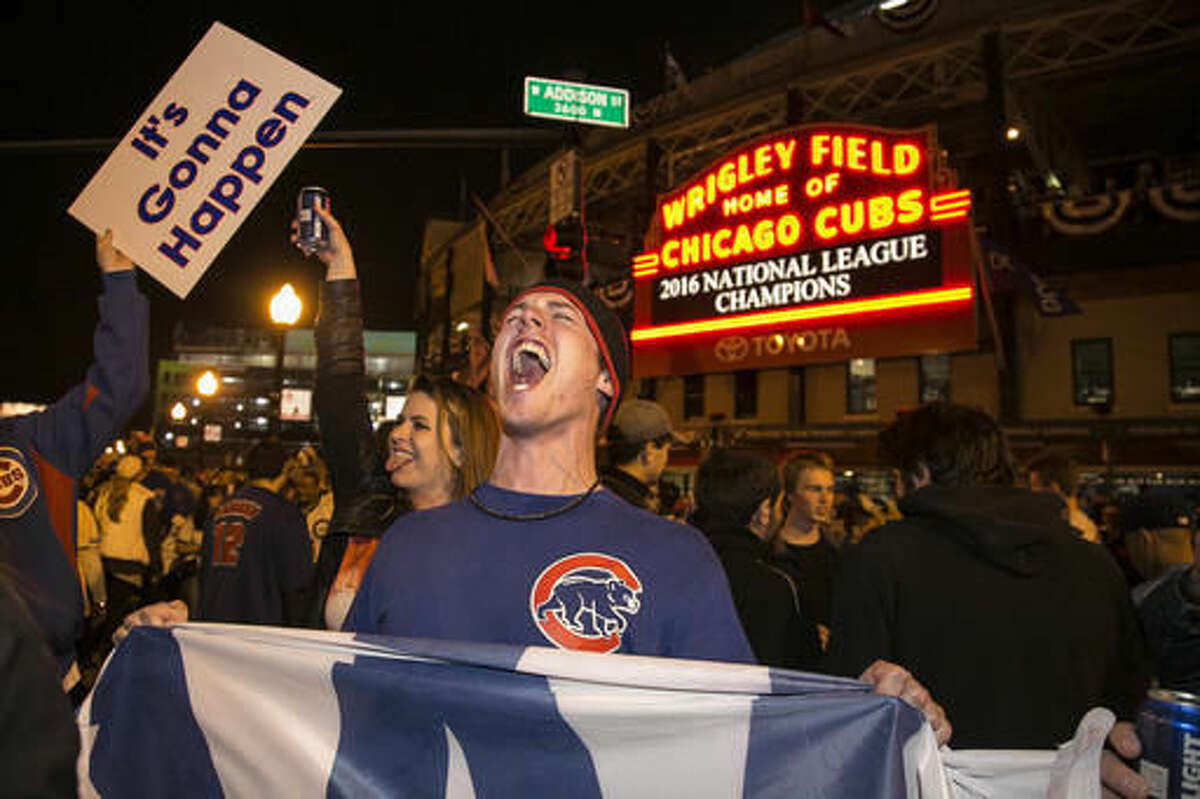 FILE - In this Oct. 22, 2016, file photo, Chicago Cubs fans celebrate outside Wrigley Field after the Cubs defeated the Los Angeles Dodgers 5-0 in Game 6 of baseball's National League Championship Series in Chicago. Fans who are hoping to see the Cubs play in the World Series for the first time since 1945 are finding that if they want a seat it will cost them what their grandparents paid for their houses. (Ashlee Rezin/Chicago Sun-Times via AP File)