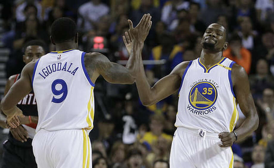 Golden State Warriors' Kevin Durant, right, is congratulated by Andre Iguodala after scoring against the Portland Trail Blazers during the first half of a preseason NBA basketball game Friday, Oct. 21, 2016, in Oakland, Calif. (AP Photo/Ben Margot)