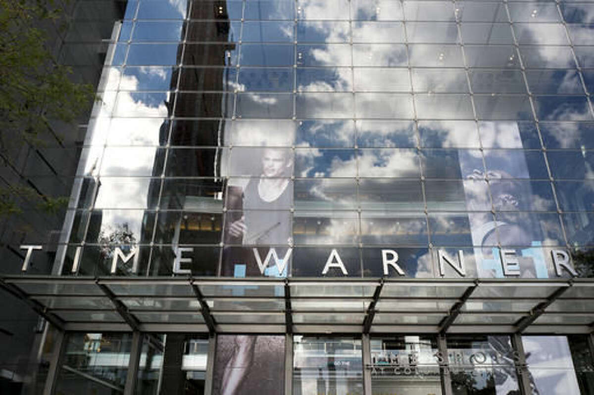 Clouds are reflected in the glass facade of the Time Warner building, Monday, Oct. 24, 2016, in New York. AT&T plans to buy Time Warner for $85.4 billion. (AP Photo/Mark Lennihan)