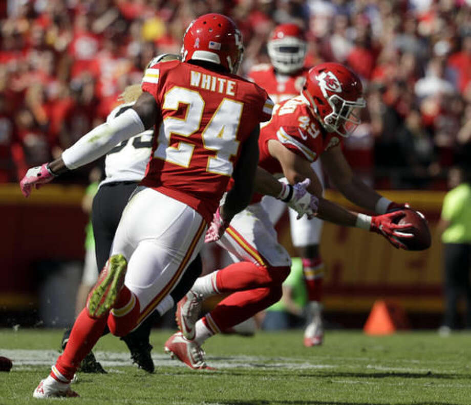 Kansas City Chiefs defensive back Daniel Sorensen (49) intercepts a throw intended for New Orleans Saints wide receiver Willie Snead IV, left rear, as defensive back D.J. White (24) watches during the first half of an NFL football game in Kansas City, Mo., Sunday, Oct. 23, 2016. (AP Photo/Jeff Roberson)