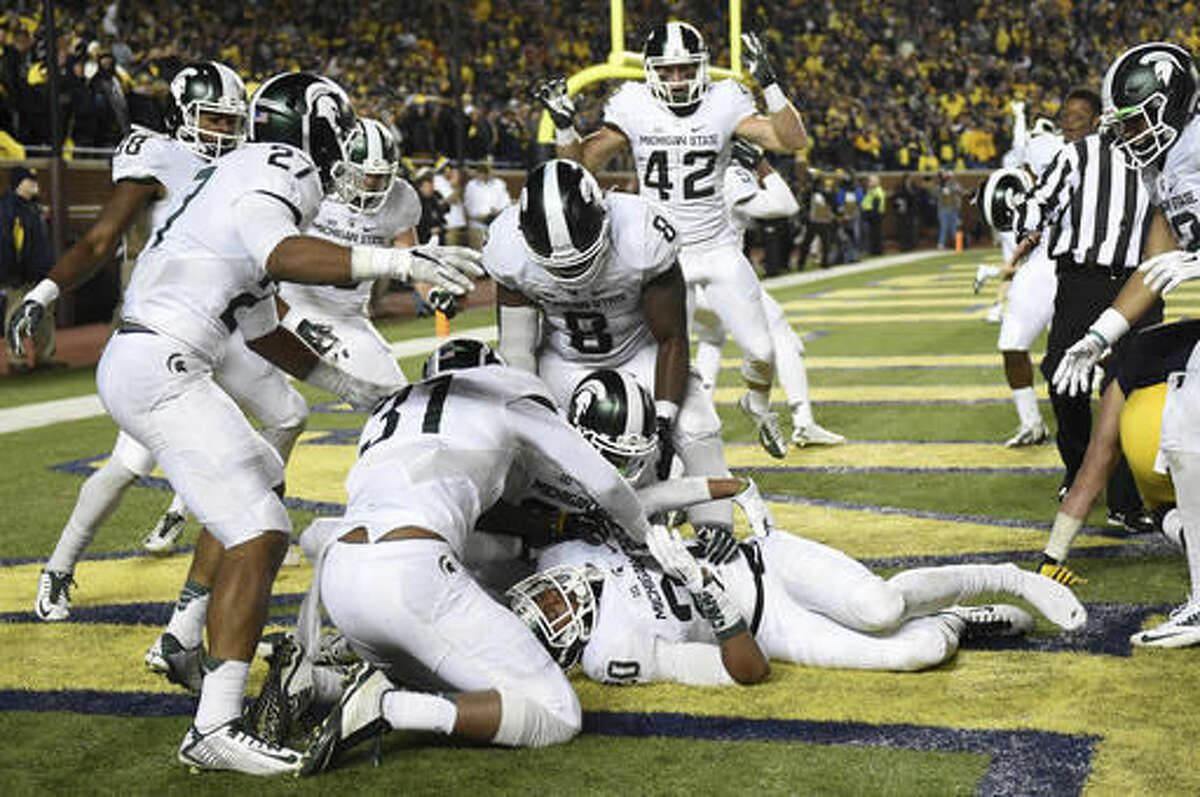 FILE - In this Oct. 17, 2015, file photo, Michigan State defensive back Jalen Watts-Jackson (20) is surrounded by teammates celebrating after he recovered a fumble on a punt in the closing seconds of the second half and returned it for a touchdown during an NCAA college football game against Michigan, in Ann Arbor, Mich. Michigan State defeated Michigan 27-23. (Melanie Maxwell/The Ann Arbor News via AP)