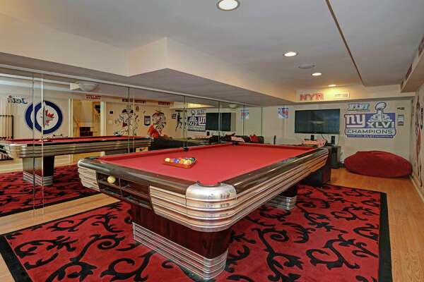 The custom-built colonial house at 60 Hitching Post Lane has a game room in its lower level that features a mirrored wall.