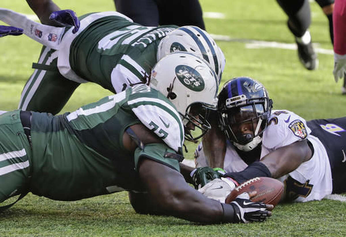 New York Jets guard James Carpenter (77) and wide receiver Brandon Marshall (15) beat Baltimore Ravens inside linebacker Zach Orr (54) to a fumbled ball during the third quarter of an NFL football game, Sunday, Oct. 23, 2016, in East Rutherford, N.J. The Jets recovered the ball on the play. (AP Photo/Frank Franklin II)