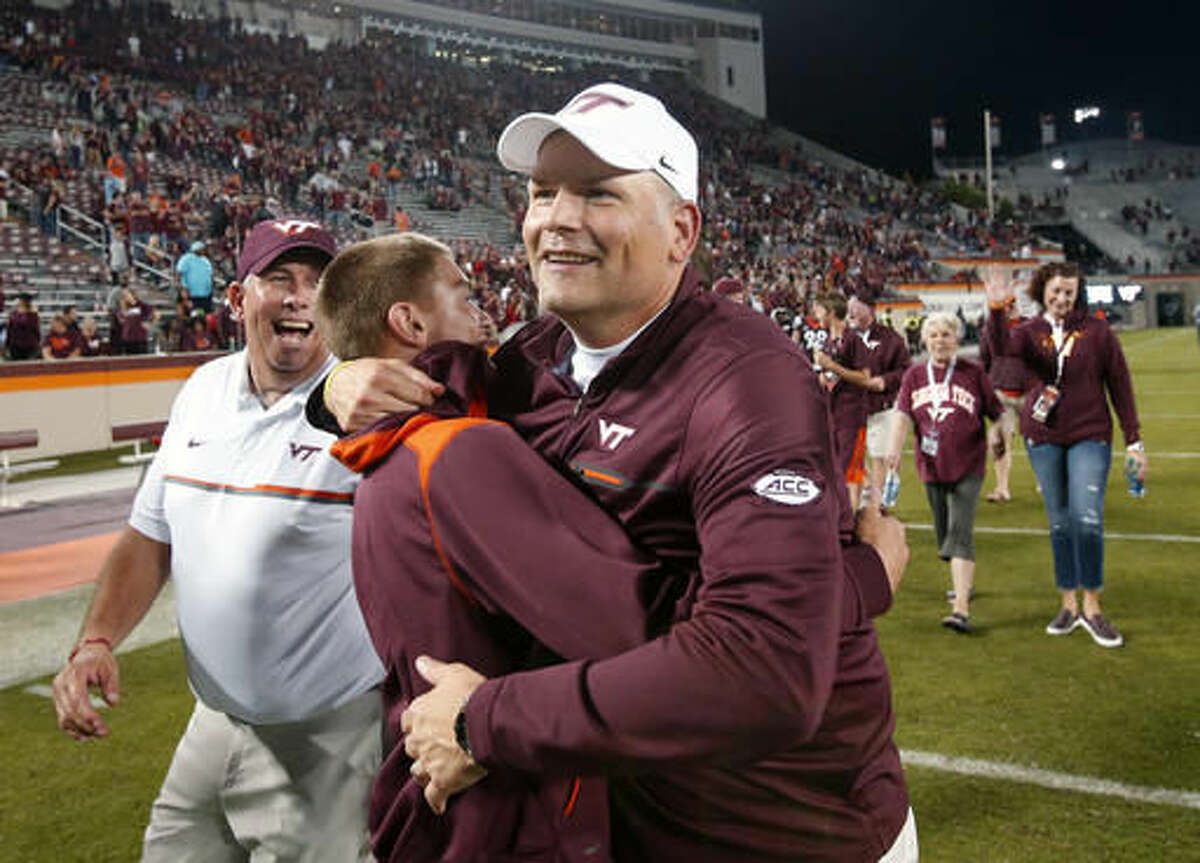 FILE - In this Oct. 20, 2016, file photo, Virginia Tech head coach Justin Fuente hugs a fan after his team defeated Miami 37-16 at Lane stadium in Blacksburg, Va. Virginia Tech has its destiny in its hands if it wants to represent the ACC's Coastal Division in the league title game. (AP Photo/Steve Helber, File)