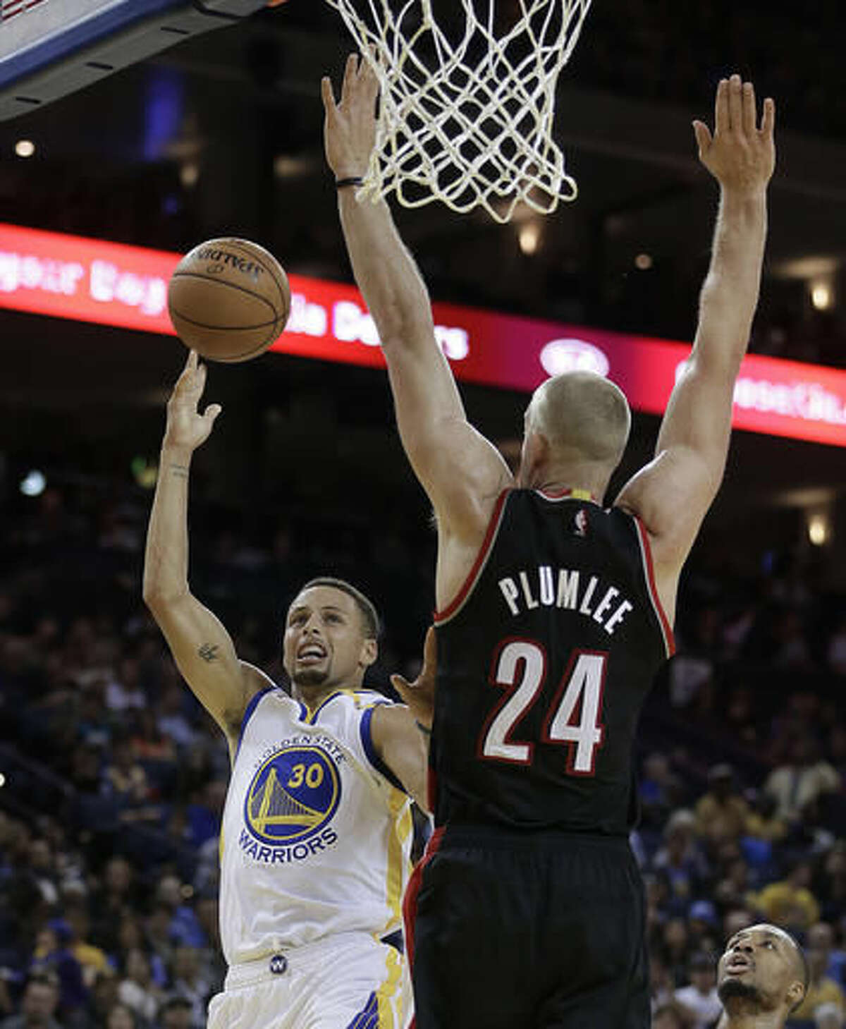 Golden State Warriors' Stephen Curry, left, shoots against Portland Trail Blazers' Mason Plumlee (24) during the second half of a preseason NBA basketball game Friday, Oct. 21, 2016, in Oakland, Calif. Warriors won, 107-96. (AP Photo/Ben Margot)