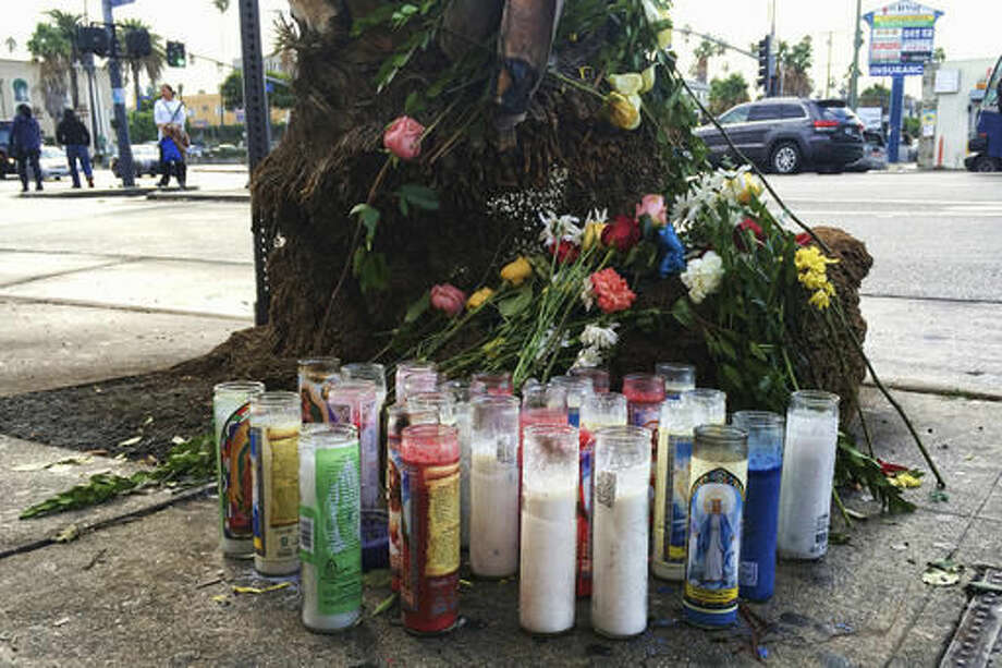 A makeshift memorial sits Monday, Oct, 24, 2016, in Los Angeles, near a tree for the victims of a vehicle collision. A tour bus returning home to Los Angeles from a casino trip slammed into the back of a semi-truck causing multiple fatalities and injuries near Palm Springs, Calif., on Sunday. (AP Photo/Alicia Chang)