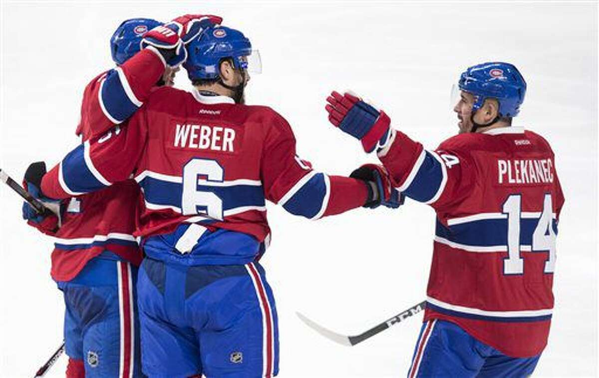 Montreal Canadiens' Shea Weber is congratulated by teammate Tomas Plekanec (14) following a goal against the Philadelphia Flyers during second period NHL hockey action in Montreal on Monday, Oct. 24, 2016. (Paul Chiasson/The Canadian Press via AP)