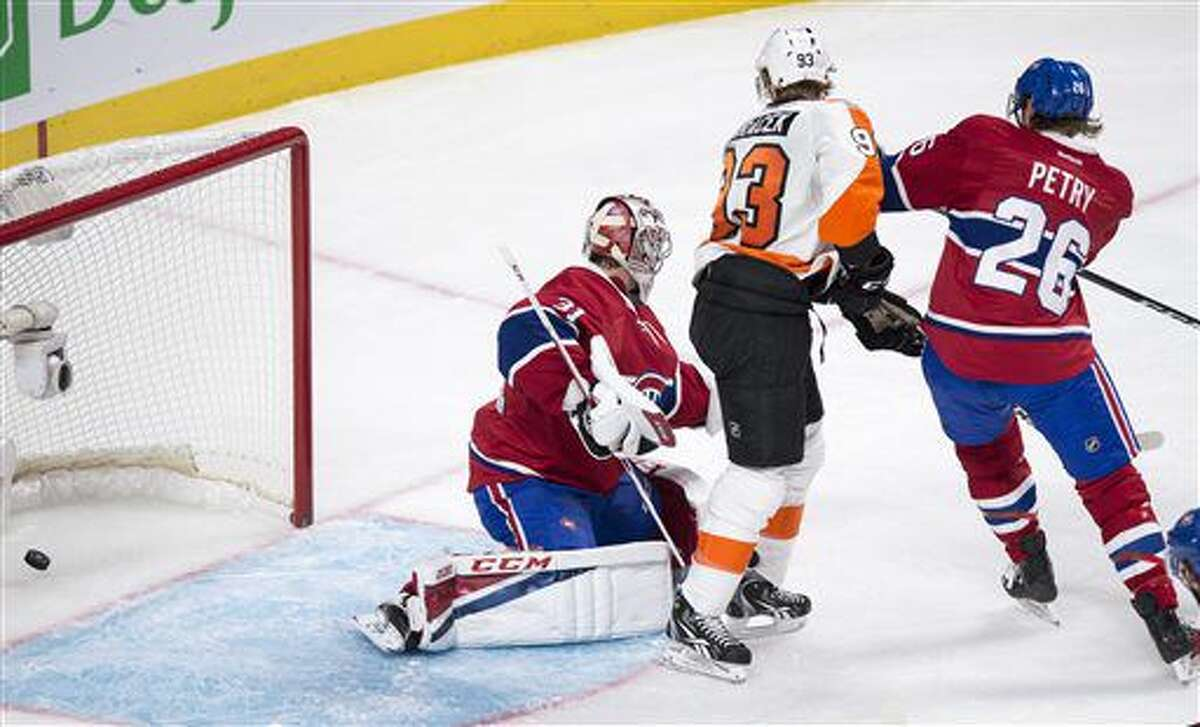 Philadelphia Flyers' Jakub Voracek (93) deflects a shot into the net past Montreal Canadiens goalie Carey Price as defenceman Jeff Petry looks on during second period NHL hockey action in Montreal on Monday, Oct. 24, 2016. (Paul Chiasson/The Canadian Press via AP)