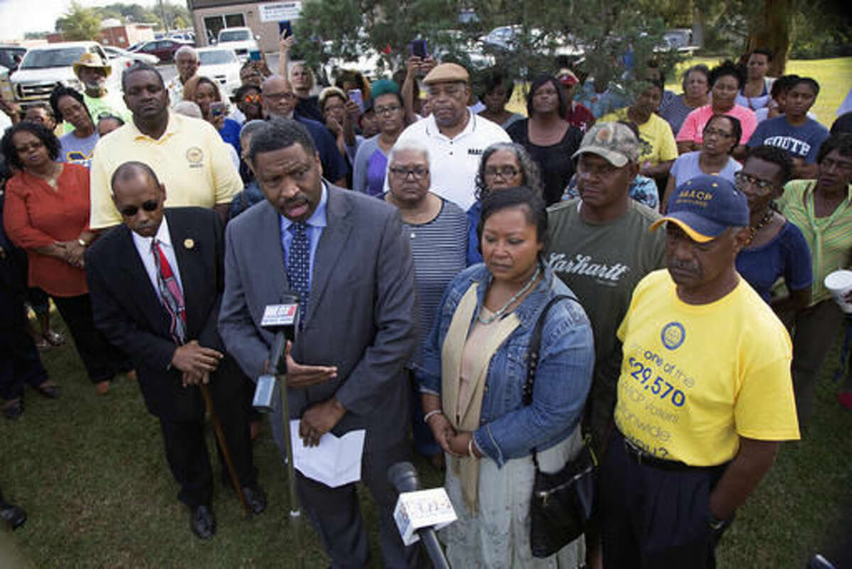 Derrick Johnson, left, president of the Mississippi NAACP, center left, talks to the media on behalf of Stacey Payton, center right, and Hollis Payton, behind his wife Stacey, in front of the Stone County Courthouse in Wiggins, Miss., Monday, Oct. 24, 2016. Johnson is demanding a federal investigation after the parents said four white students put a noose around their son's neck at school. (AP Photo/Max Becherer)