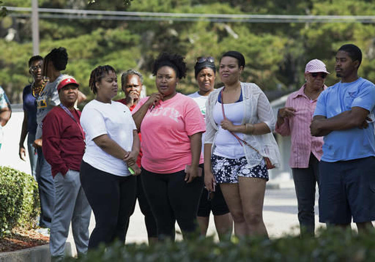 Members of the community gather before Derrick Johnson, left, president of the Mississippi NAACP, speaks in front of the Stone County Courthouse in Wiggins, Miss., Monday, Oct. 24, 2016. Johnson is demanding a federal investigation after the parents of a black high school student said four white students put a noose around their son's neck at school. (AP Photo/Max Becherer)
