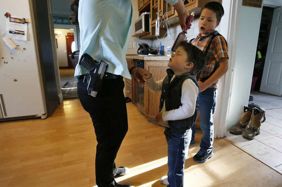"Gun-rights advocate, restaurant owner and mother of four sons, Lauren Boebert, wears her usual gun on her hip as she brushes the hair of Roman, 3, as the family gets ready to leave home for church in Rifle, Colo., on May 1, 2016. ""When we first opened Shooters Grill, we were one month in, and I was there alone a lot, and there was actually a man who was beat to death in the alley. He lost his life that night, and it kinda shook me up. I was there alone a lot and I thought, 'what am I gonna do, what am I gonna do if something happens, what if somebody comes in here, my husband isn't here to protect me, I'm all alone,' and really, that's what got me to open-carry."" (AP Photo/Brennan Linsley)"