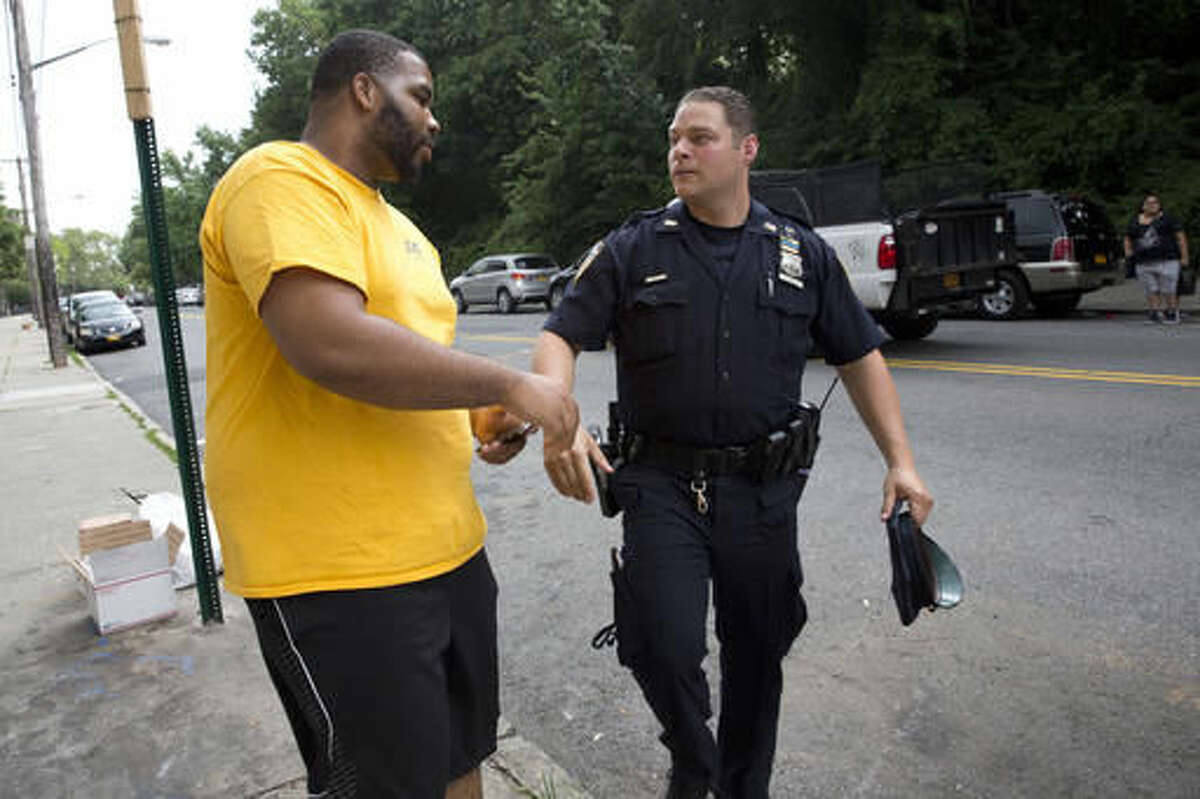 """Police officer Jessi D'Ambrosio, right, of the 120th precinct in the Staten Island borough of New York, speaks to a resident while on patrol at the Richmond Terrace Houses, Thursday, July 7, 2016. D'Ambrosio, 32, and his partner, Mary Gillespie, 28, are the new """"neighborhood coordinating officers"""" for the six-building project where Eric Garner once lived. Jersey Street, with a reputation for crime, runs the length of a complex, most of whose residents are black. """"We want them to feel comfortable with us and that's what we're building on,"""" Gillespie says. (AP Photo/Mary Altaffer)"""