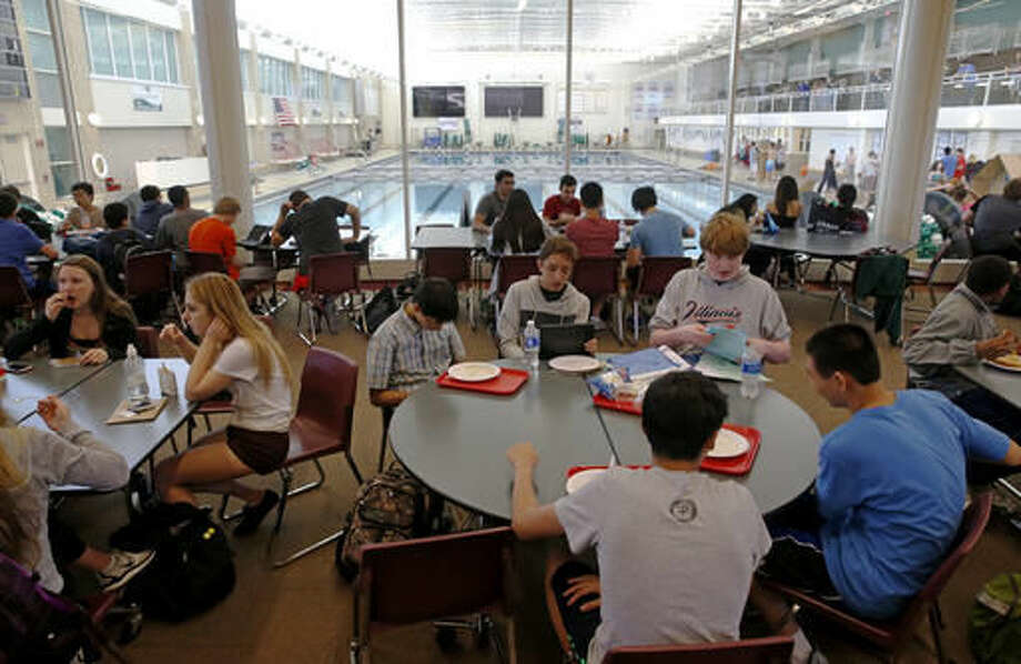Students gather between classes in a lounge area overlooking an Olympic-size pool at Stevenson High School in Lincolnshire, Ill., on May 24, 2016. A study for the non-profit and non-partisan National Bureau of Economic Research tracked students enrolled in districts where there was a prolonged increase in school funding. Students educated in flush times finished more years of school, were less likely to live in poverty as adults, and made about 7.25 percent more in wages. (AP Photo/Nam Y. Huh)