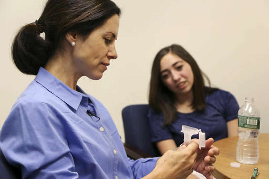 In this July 7, 2016, photo, Erin Lopes gives a saliva sample for genetic testing while her daughter Evee Bak looks on at the Seaver Autism Center at Mount Sinai Hospital in New York. Lopes' son Tommy was diagnosed at age 3 with autism. (AP Photo/Seth Wenig)