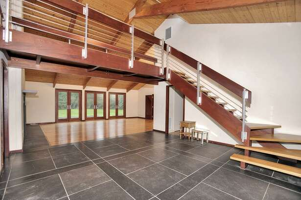 The foyer of this contemporary house features a vaulted ceiling, floating staircase and stone floor.