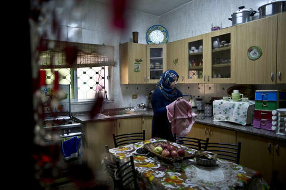 In this Monday, March 21, 2016 photo, Jordanian plumber Maryam Mutlaq, 41, works in the kitchen of her home in Zarqa. It has been a challenge just to come this far as a plunber in an ultra-conservative community where many women don't work outside the home at all. Even Mutlaq's children, who cheer her on from the audience today, fiercely opposed her choice at first. The coming months will determine if she can overcome the odds and turn her bold dream into a real-life business. (AP Photo/Muhammed Muheisen)