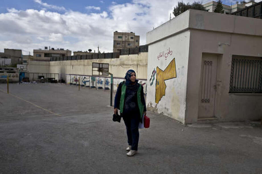 In this Monday, March 21, 2016 photo, Jordanian plumber Maryam Mutlaq, 41, arrives to a school in Zarqa. Mutlaq's choice of career is rare for the Arab world where traditional gender roles make men the main breadwinners and confine most women to certain jobs _ teachers, nurses, low-level government clerks. Five years ago, the Arab Spring brought the hope of more opportunities for women. Yet that promise has not panned out, analysts and activists say, and in some cases spreading violence has even led to a backlash. (AP Photo/Muhammed Muheisen)