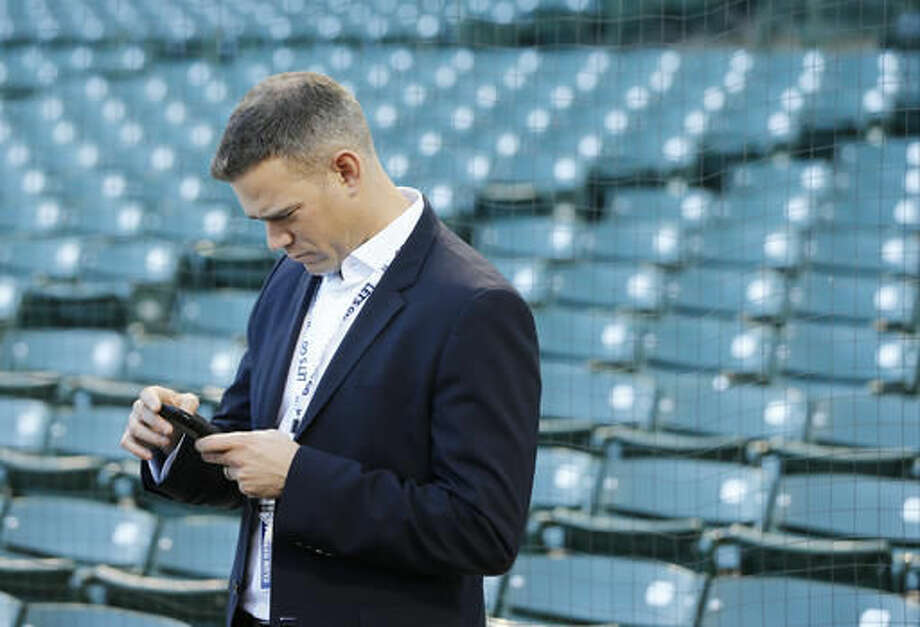 Chicago Cubs president for baseball operations Theo Epstein texts during batting practice before Game 6 of the National League baseball championship series against the Los Angeles Dodgers, Saturday, Oct. 22, 2016, in Chicago. (AP Photo/Charles Rex Arbogast)