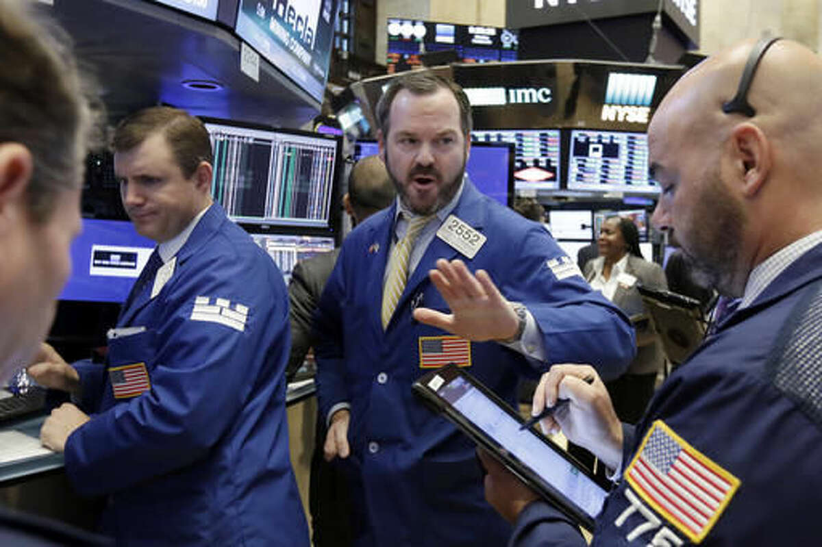 Specialist Charles Boeddinghaus, center, works with traders on the floor of the New York Stock Exchange, Monday, Oct. 24, 2016. Stocks are opening higher on Wall Street as traders looked over a big batch of corporate deals. (AP Photo/Richard Drew)