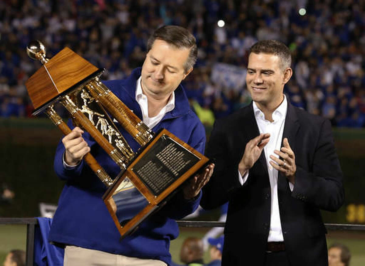 Chicago Cubs owner Tom Ricketts holds up trophy as president for baseball operations Theo Epstein watches after Game 6 of the National League baseball championship series against the Los Angeles Dodgers Saturday, Oct. 22, 2016, in Chicago. The Cubs won 5-0 to win the series and advance to the World Series against the Cleveland Indians. (AP Photo/Nam Y. Huh)