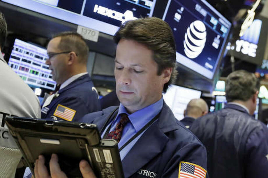 Trader Patrick McKeon, center, works on the floor of the New York Stock Exchange, Monday, Oct. 24, 2016. Stocks are opening higher on Wall Street as traders looked over a big batch of corporate deals. (AP Photo/Richard Drew)