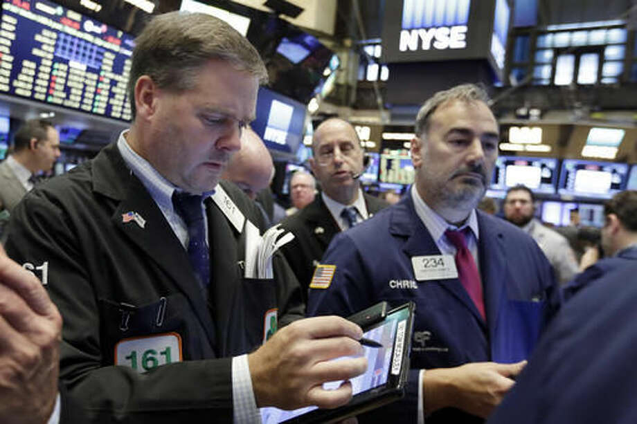 Thomas McCauley, left, works with fellow traders on the floor of the New York Stock Exchange, Monday, Oct. 24, 2016. Stocks are opening higher on Wall Street as traders looked over a big batch of corporate deals. (AP Photo/Richard Drew)