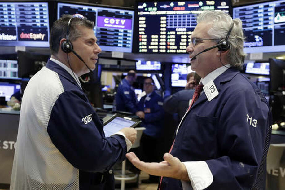 Traders William McInerney, left, and Frank O'Connell work on the floor of the New York Stock Exchange, Monday, Oct. 24, 2016. Stocks are opening higher on Wall Street as traders looked over a big batch of corporate deals. (AP Photo/Richard Drew)