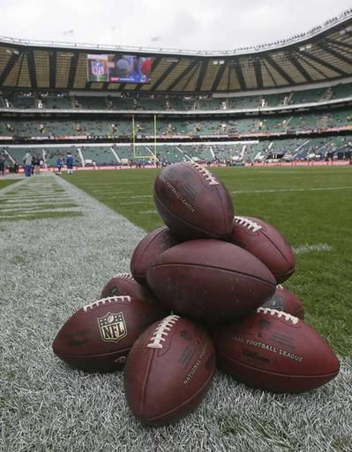 A pile of footballs are placed on the touchline during the warm-up before an NFL football game between New York Giants and Los Angeles Rams at Twickenham stadium in London, Sunday Oct. 23, 2016. (AP Photo/Tim Ireland)
