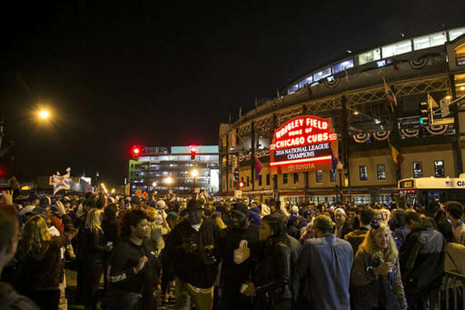 People congregate outside Wrigley Field after the Chicago Cubs defeated the Los Angeles Dodgers 5-0 in Game 6 of baseball's National League Championship Series, Saturday, Oct. 22, 2016, in Chicago. The Cubs advanced to the World Series. (Ashlee Rezin/Chicago Sun-Times via AP)