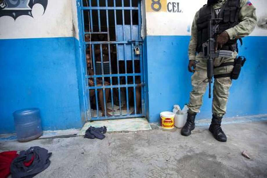 A police officer stands outside a room of inmates after a prison break at the Civil Prison in the coastal town of Arcahaiea, Haiti, Saturday, Oct. 22, 2016. Over 100 inmates escaped after they overpowered guards who were escorting them to a bathing area. (AP Photo/Dieu Nalio Chery)